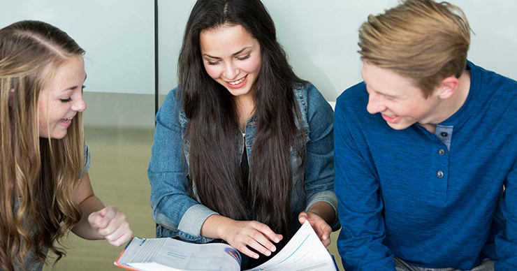 Three students looking through a textbook